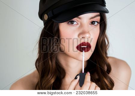 Seductive Pretty Young Brunette Woman Using Lip Brush For Applying Red Lipstick To Her Lips. Adverti