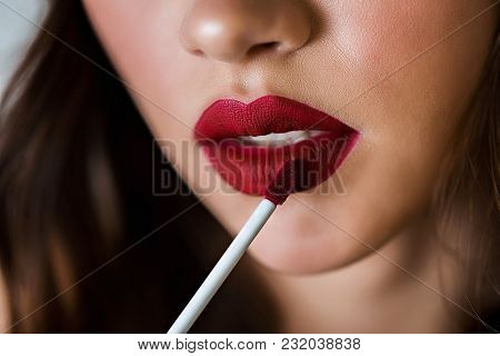 Seductive pretty young brunette woman using lip brush for applying red lipstick to her lips. Advertising lipstick, lip gloss, cosmetics. Make up, makeup artist, beauty blogger poster