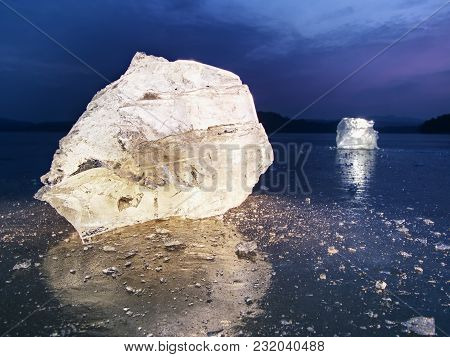 Blocks Of Shining Ice And Snow On The Shore. The Floes And Crushed Ice  During The Evening And Dark