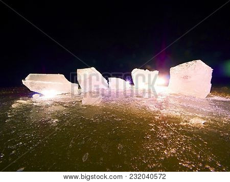 Melting Pieces Of Chopped Ice Blocks. Strong Colorful Backlight Shine Deep Cracks, Low Angle View. F
