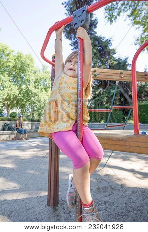 Girl Hanging On Bar In Playground And Mother Watching