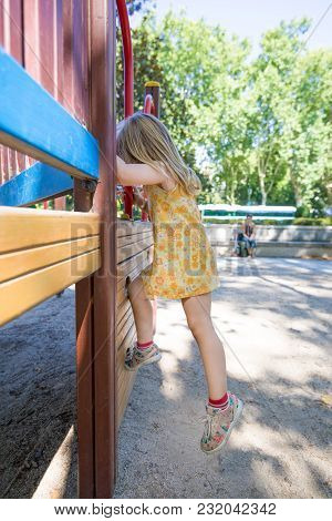 Little Girl Climbing In Playground And Mother Watching
