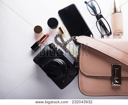 Flat lay of beige leather woman bag  with cosmetics, accessories, camera and smartphone on white background.