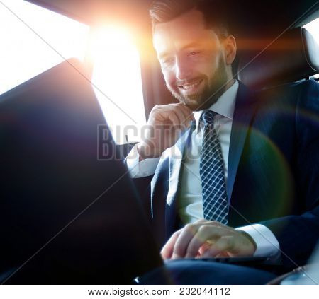 Caucasian male business executive travelling by a car and working on laptop computer.