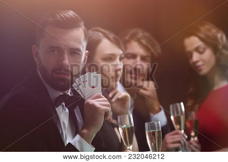 Poker player to four aces over dark background