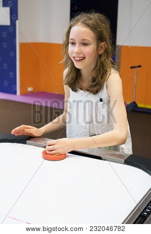 Cute Little Girl Playing Table Hockey Game.