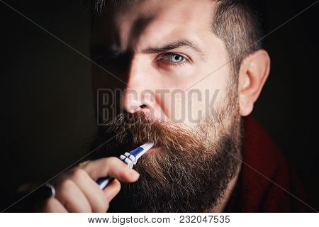 Serious Bearded Man In White T-shirt Brushing Teeth Against A Black Background. Caucasian Adult Man