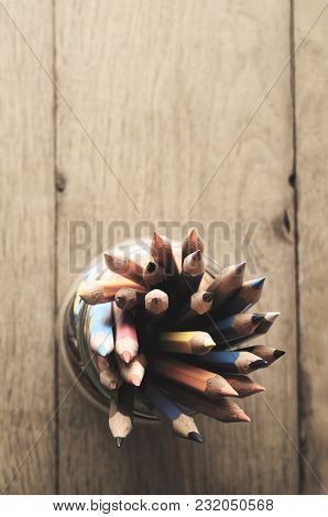 Overhead Shot Of Multiple Art Pencils In Many Colours, Grouped In A Glass Jar On Oak Wood Planked Ta