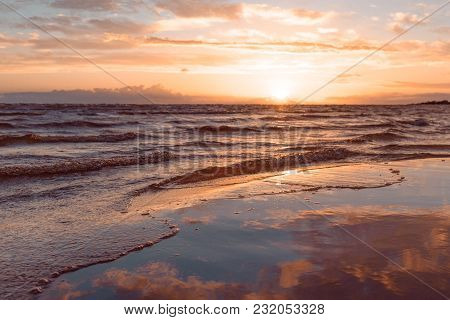 Horizontal Shot Of The Wave At Sunset Lapping On A Sandy Beach Against The Sea In Blur. Tonted Orang