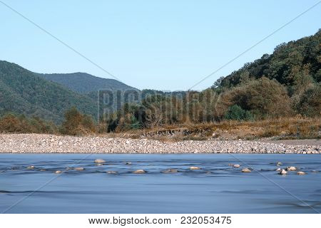 Horizontal Shot Of The River In The Valley On The Background Of Mountains And Blue Sky. Long Exposur