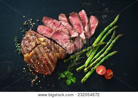 Roasted rib eye steak with green asparagus on old sheet