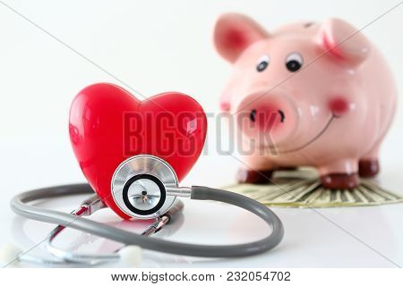 Phonendoscope Head Lying On Table With Red Toy Heart Closeup And Funny Piggybank Standing In Backgro
