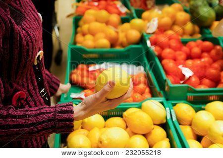 Woman Chooses Lemons In A Supermarket. Copy Paste