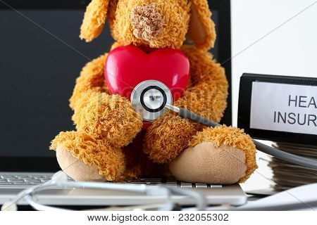Teddy Bear Holding Toy Red Heart Listening With Phonendoscope Head Closeup At Doctor Workplace Instr