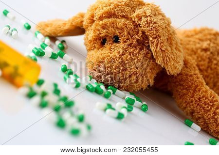 Teddy Bear Lie With Big Pile Of Tablets Fell Out From Container Jar Closeup. Paediatrics Terminal Si