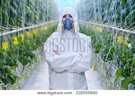 Waist Up Portrait Of Plantation Worker Wearing Protective Hazmat Suit And Mask Posing With Arms Cros