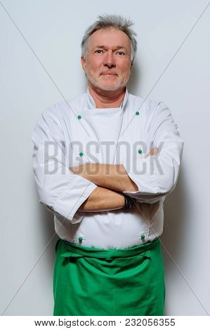 Portrait Of A Smiling Chef On A Gray Background. Looking Camera. Adult Man, An Experienced Chef In A