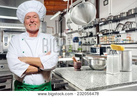 Portrait Of A Smiling Chef On A Kitchen Background. Looking Camera. Adult Man, An Experienced Chef I