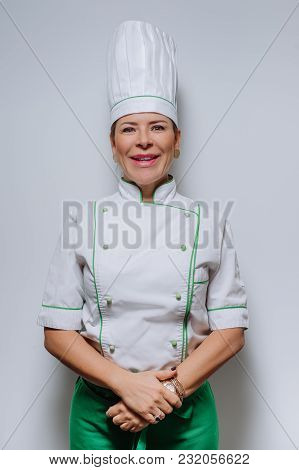 Studio Portrait Of A Beautiful Woman Chef In Uniform. A Happy, Smiling Woman Cook In A Cap And Unifo