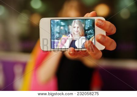 Girl With Shopping Bags On Screen At Phone.