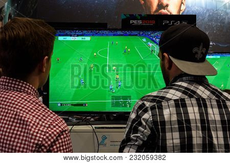 Cologne, Germany - August 24, 2017: Two Fair Visitors Play The Game Pro Evolution Soccer At The Boot