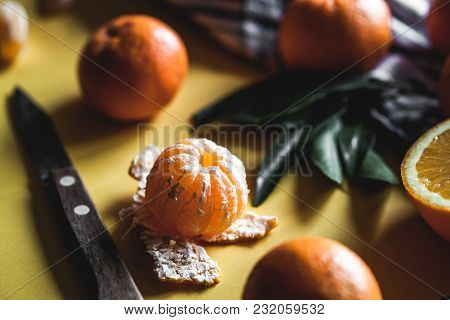 Fresh Clementines, Oranges On Board With Green Leaves With A Knife. Top View On A Yellow Background