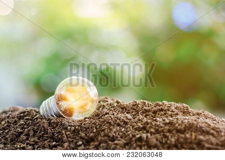 Glowing Light Bulb On Soil Against Blurred Natural Green Background With Copy Space For Saving Energ