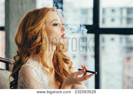 Attractive Young Redheaded Woman Smoking Electronic Cigarette.