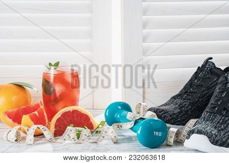 Fresh Grapefruits And Grapefruit Juice, Dumbbell And Measuring Tape, On Rustic White Wooden Table Op