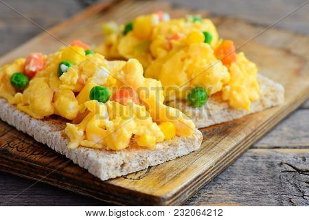 Scrambled Eggs Omelette. Homemade Scrambled Eggs Omelette With Vegetables On Crispy Bread Toasts. He