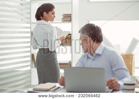 Female Office Worker. Beautiful Pleasant Young Woman Standing Near The Shelf And Holding A Book Whil