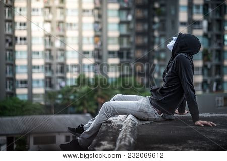 Mystery Man In White Mask Wearing Hoody Sitting On Rooftop Of Abandoned Building And Look Up In The
