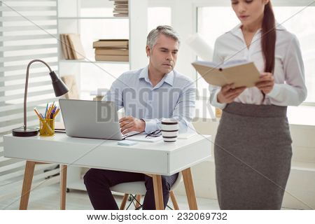 Sexual Attraction. Serious Nice Adult Man Sitting At The Table And Looking At His Colleague While Ha