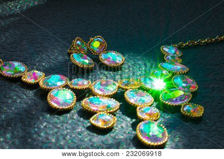 A Luxurious Gold Necklace With Colored Iridescent Stones On A Dark Black Background. Stones Of Vario