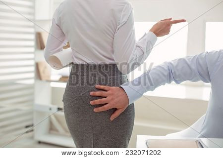 Sexual Harassment. Close Up Of A Male Hand Touching A Woman While Harassing Her At Work