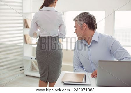 Beautiful Woman. Serious Nice Adult Man Sitting At The Table And Staring At His Female Colleague Whi