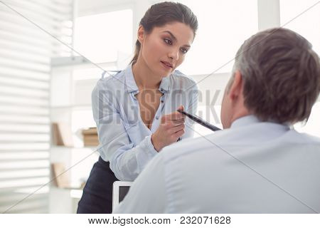 Sexual Behavior. Attractive Pleasant Nice Woman Looking At Her Colleague And Holding His Tie While B