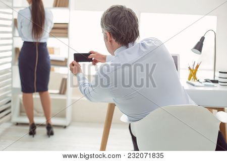 Sexual Harassment. Nice Good Looking Adult Man Sitting At The Table And Holding A Smartphone While T