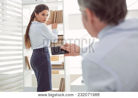 Uncomfortable Situation. Unhappy Cheerless Young Woman Standing Near The Shelf And Putting Books The