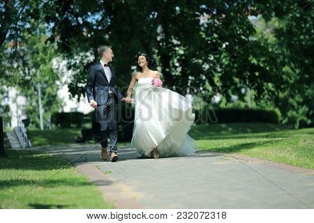 Newlywed Couple Walking In The Park The Day Of The Wedding.outdoors