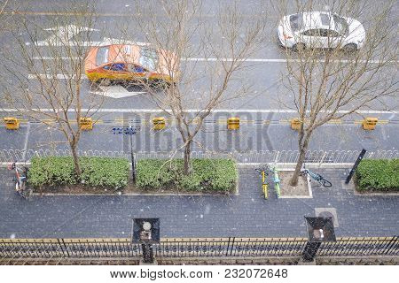 Aerial View Of A Walkway And Two Cars On A Road During Snowy Day. Rare Snowy Day In Chaoyang Distric