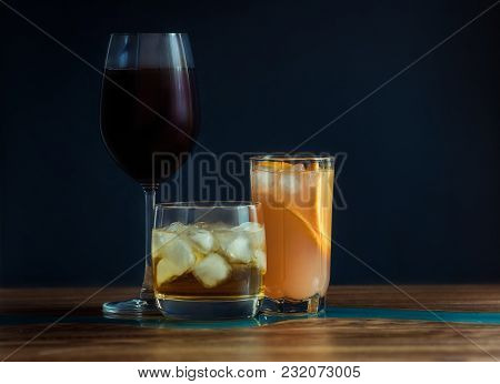 Alcohol Drinks (red Wine, Whisky, Grapefruit Cocktail) On Dark Solid Blue Background