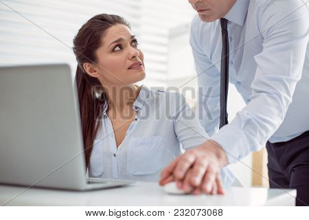 Harassment At Work. Unhappy Nice Young Woman Sitting At The Table And Looking At Her Boss While Bein