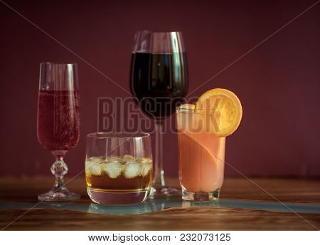 Alcohol Drinks (red Wine, Sparkling Wine, Whisky, Grapefruit Cocktail) On Dark Solid Red Background