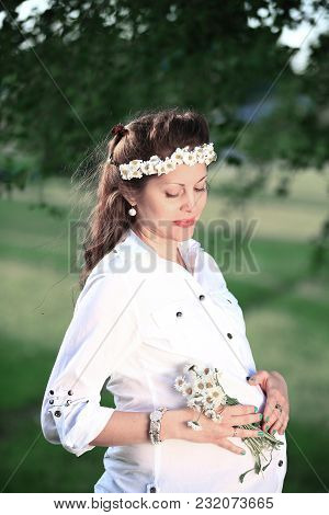 Pregnant Woman In A Wreath And A Bouquet Of Wild Flowers On A Walk In The Park On A Sunny Day