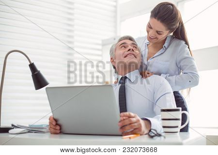 How Do You Feel. Pleasant Nice Young Woman Standing Behind Her Colleague And Smiling While Doing A M