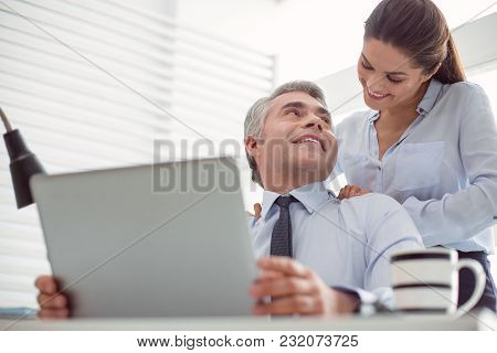 Personal Relationships. Cheerful Positive Nice Woman Standing Behind Her Boss And Smiling While Doin
