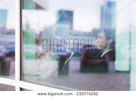 Photo From Behind The Glass: A Successful Business Team Stands In Front Of A Window In A Modern Offi