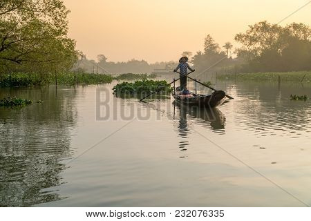 Vietnamese Woman Rowing Wooden Boat On River