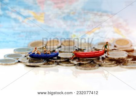 Miniature People, Children With Paddle Boat On Coins. Concept Of Travel Busines.